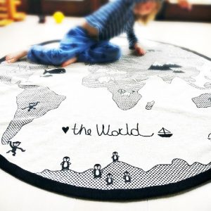boy sitting on an oyoy world adventure rug