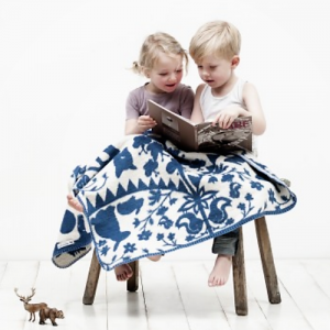 Boy and girl sitting under a fabulous goose organic blanket
