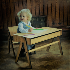 Little girl writing at a We Do Wood childrens desk